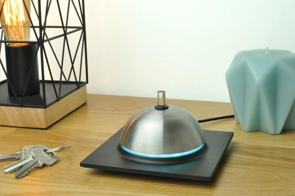 Inspiré de la sonnette de comptoir des grands hôtels, le design de Concierge est signé Adrien Ciejak d'Unistudio. Son bouton en fibre de verre et son anneau lumineux diffusent un halo de lumière qui alerte d'événements dans la journée (météo, réception d'un colis…).