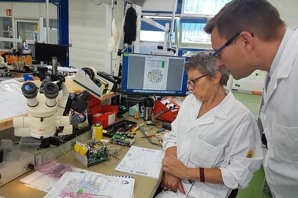 Nathalie Guede, opératrice à Anjou Electronique, et Arnaud Goulet, le directeur général de la PME, observent un gain de temps entre la fiche numérique et les différentes informations sur papier. ©CGM