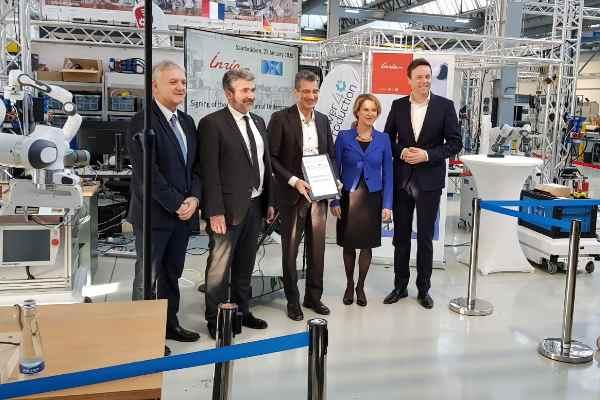 La cérémonie a eu lieu à Sarrebruck au laboratoire d'innovation Power4Production, en présence du Ministre-Président du Land de Sarre, M. Tobias Hans, et de Mme. Heike Raab, Secrétaire d'Etat, représentante du Land de Rhénanie-Palatinat auprès du gouvernement fédéral pour l'Europe, les médias et le numérique.